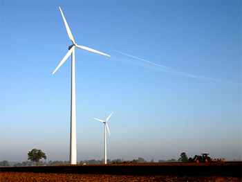 Two wind turbines stand tall against a rich blue sky